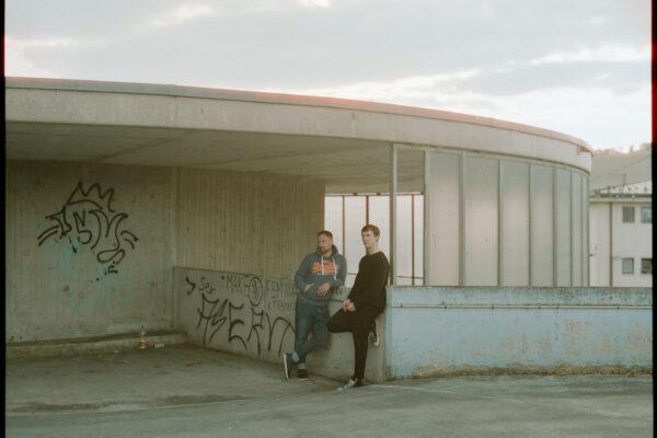 Zwei Männer stehen an urbanem Parkplatz Analog Mittelformat Cinestill