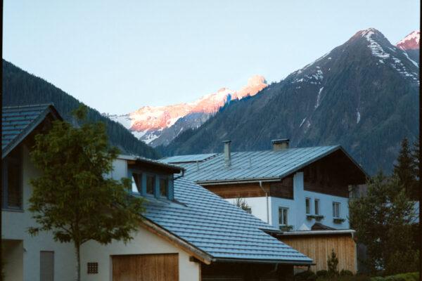 Analogfoto eines Berges mit Häusern in Österreich mit Alpenglühen