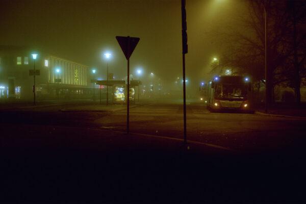 Bahnhof mit Neonröhren bei Nacht und Bus Nebel